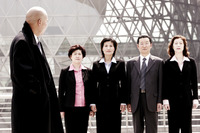 A bald man watching a group of business people standing in a row