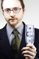 A bespectacled man in business suit holding a banknote