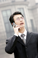 A bespectacled man in business suit talking on the hand phone