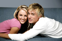 A couple lying on the couch flashing a smile at the camera