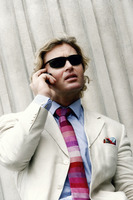 A guy in business suit and sunglasses talking on the hand phone