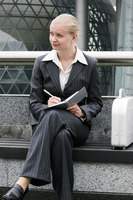 A lady in business suit sitting on the bench writing notes