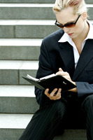 A lady in business suit with sunglasses sitting on the stairs writing her organizer