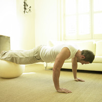 A man doing push up with fitness ball