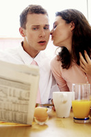 A man getting a kiss from his wife while having breakfast and reading newspaper