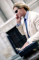 A man in business suit and sunglasses talking on the hand phone with an opened suitcase in front of him