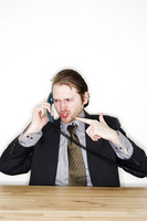 A man in business suit talking angrily on the phone