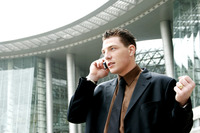 A man in business suit talking on the hand phone