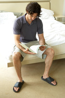 A man sitting on the bed reading documents