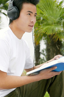 A man sitting on the lakeside listening to music on his headphone while reading a book