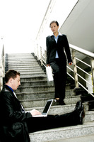 A man sitting on the stairs using laptop while a woman walking down the stairs