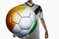 A soccer player holding ivory coast soccer ball