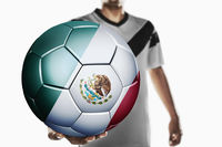 A soccer player holding mexico soccer ball