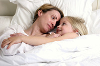A woman and her daughter lying down on the bed looking at each other
