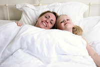 A woman and her daughter lying on the bed together