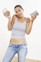 A woman in jeans holding up two tins of paint