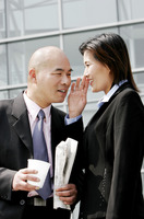 A woman whispering something to a bald man