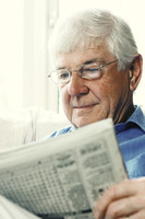 An old bespectacled man reading newspaper