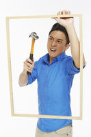 Angry man hitting a picture frame with hammer