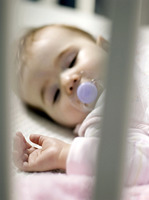 Baby girl with pacifier sleeping in the crib