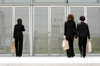 Back shot of three business women walking into a building