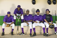 Baseball team sitting in dugout (portrait)