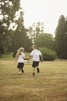 Boy and girl holding hands while running in the park