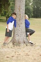 Boy and girl leaning against tree