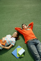 Boy and girl lying on the field