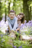 Boy and girl sitting on tree root