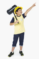 Boy holding a toy hammer and pointing to the left