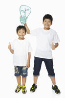 Boy holding up a cut out light bulb over another boy's head