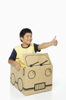 Boy in cardboard bus showing hand gesture