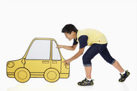 Boy pushing a cardboard car