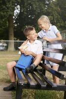 Boy sitting on bench holding sandwich, girl smiling at him