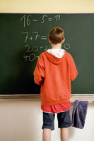Boy solving an equation on the blackboard