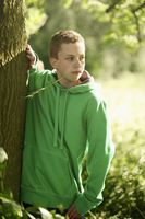 Boy standing next to a tree and looking away