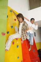 Boys climbing rock wall