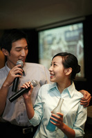 Business people singing karaoke after work