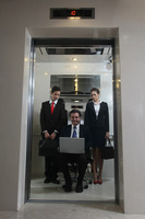 Business people watching businessman sitting on office chair and using laptop in an elevator