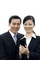 Businessman and businesswoman looking at mobile phone