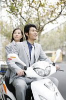 Businessman and businesswoman riding on a scooter