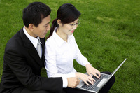 Businessman and businesswoman sharing a laptop