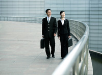 Businessman and businesswoman with briefcase walking together