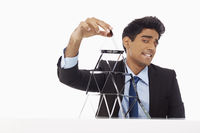 Businessman building a pyramid of cards