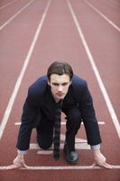 Businessman crouching at starting line of track