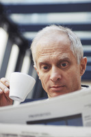 Businessman drinking coffee while reading newspaper