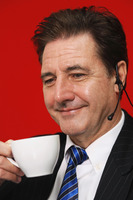 Businessman drinking coffee while talking on the telephone headset