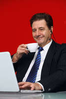Businessman drinking coffee while video conferencing on laptop