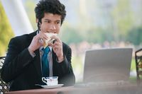 Businessman eating sandwich while looking at the laptop